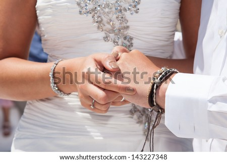 hands of wedding couple changing rings