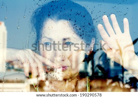 Hands of woman at the window - stock photo