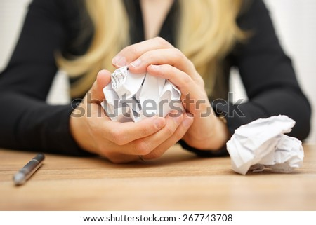 Hands of woman crumple sheets of paper at the table - stock photo