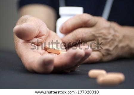 Hands Of Woman Deformed From Rheumatoid Arthritis holding pills - stock photo