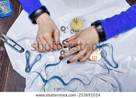 Hands of woman designer at work on the desk. Fabric, buttons and needles on the table. Person is not recognizable.