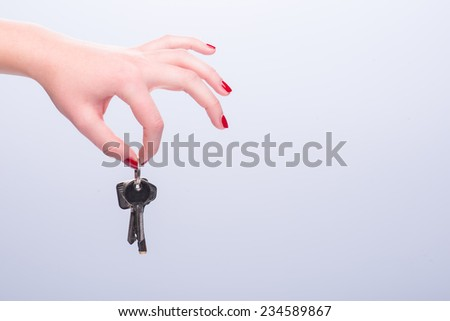 Hands of woman giving someone keys isolated on white background.  Concept of new life