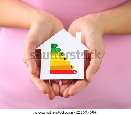 Hands of woman holding paper house with energy efficiency chart - stock photo