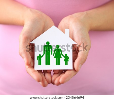 Hands of woman holding paper house with family - stock photo