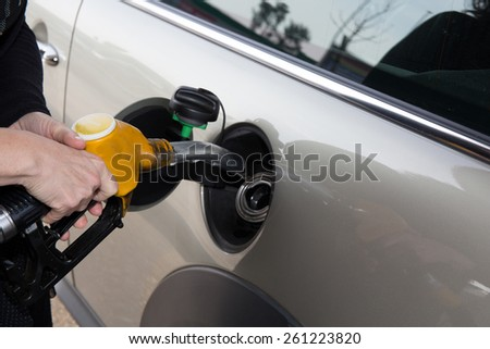 hands of woman refueling her car at the gas station - stock photo