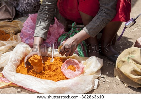 Hands of woman selling spices in an Ethiopian market - stock photo