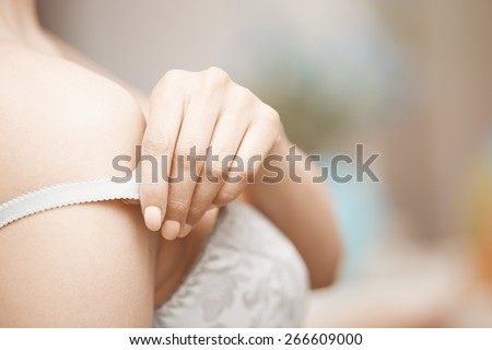 Hands of woman undressing brassiere. Close-up photo - stock photo