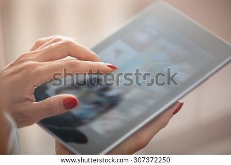Hands of woman using digital tablet - stock photo