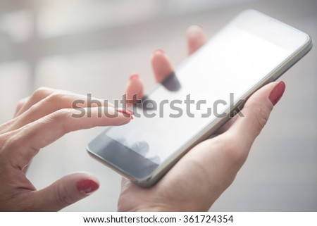 Hands of woman using smartphone