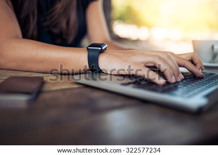 Hands of woman wearing smartwatch on the keyboard of her laptop computer. Female working on laptop in a cafe. - stock photo