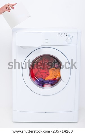 Hands of woman with detergent. Washing machine on the white background. - stock photo
