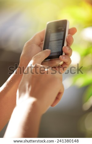 Hands of woman with smartphone in the garden - stock photo