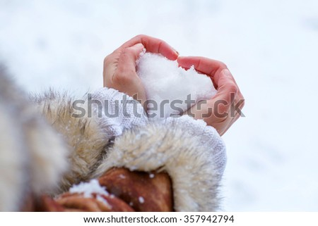 Hands of woman with snow heart in winter. Symbol of love. - stock photo