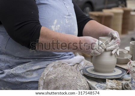 Hands of woman working on pottery wheel - stock photo