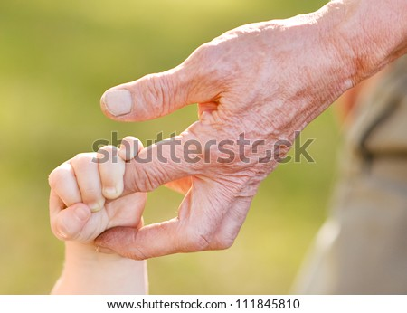 hands of young child and old man - stock photo