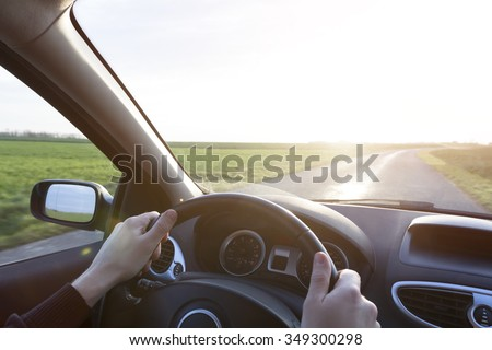 Hands of young driver on steering wheel during road trip with rental car - stock photo