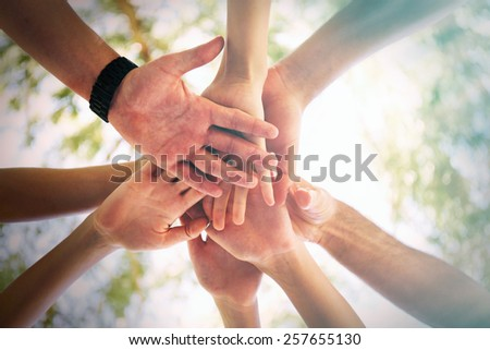 Hands of young people close up on sunny nature background