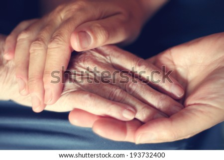 Hands of young woman and elderly woman - stock photo