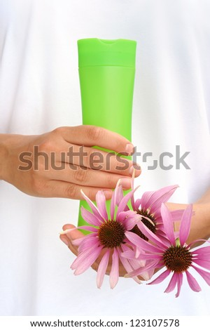 Hands of young woman holding cosmetics bottle and fresh coneflowers
