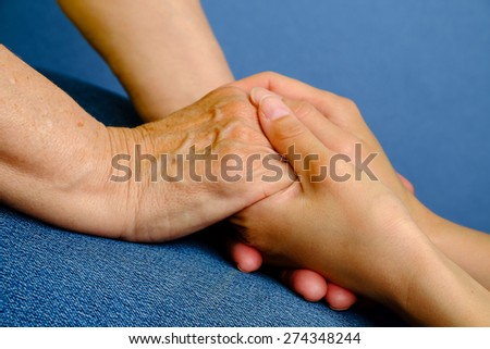 Hands of young woman holding hands of an elderly woman - stock photo