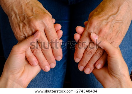 Hands of young woman holding hands of an elderly woman, top view - stock photo