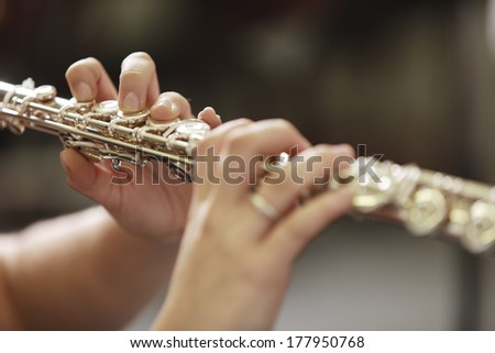 Hands of young woman playing the flute  - stock photo