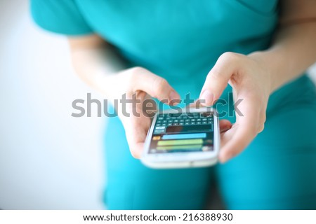 Hands of young woman sending text message from smart phone at work - stock photo