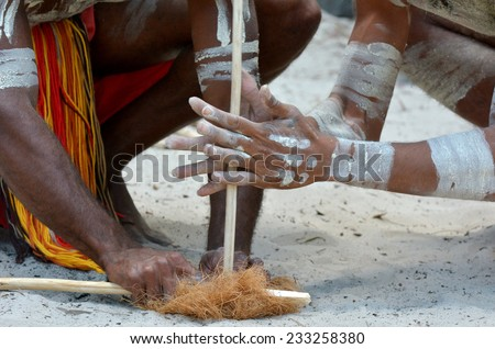 Hands of Yugambeh Aboriginal warriors men demonstrate  fire making craft during Aboriginal culture show in Queensland, Australia. - stock photo