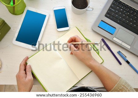 HANDS ON A DESK WITH COMPUTER, PHONE AND COFFEE - stock photo