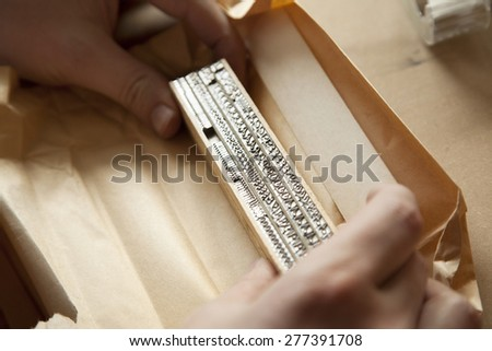 Hands on a typeface for use with a letterpress machine.  - stock photo