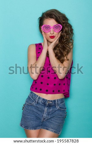 Hands on cheeks. Beautiful young woman posing with hands on cheeks. Three quarter length studio shot on teal background. - stock photo