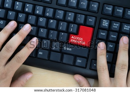 "Hands on computer keyboard with ""Access Granted"" words at enter button. - stock photo"