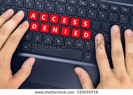 """Hands on laptop with """"ACCESS DENIED"""" words on keyboard buttons. - stock photo"""