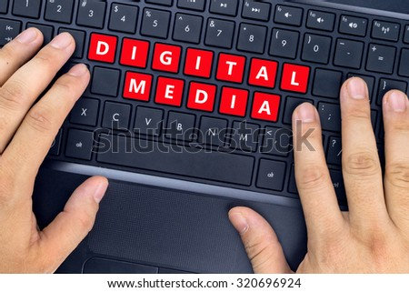 "Hands on laptop with ""DIGITAL MEDIA"" words on keyboard buttons. - stock photo"