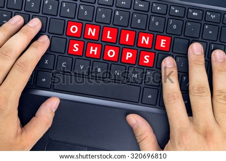 """Hands on laptop with """"ONLINE SHOPS"""" words on keyboard buttons. - stock photo"""
