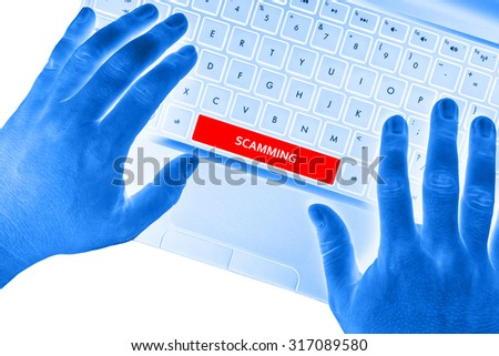 """Hands on laptop with """"SCAMMING"""" word on spacebar button on white background. - stock photo"""