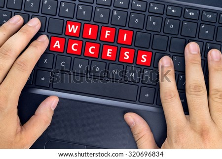 """Hands on laptop with """"WIFI ACCESS"""" words on keyboard buttons. - stock photo"""