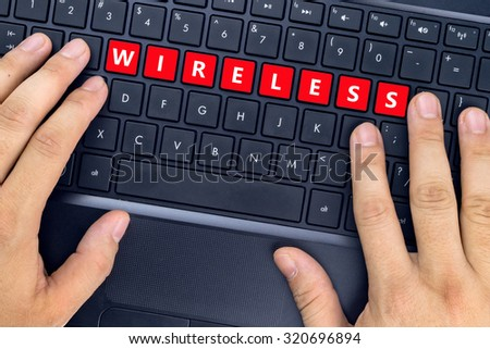 "Hands on laptop with ""WIRELESS"" word on keyboard buttons. - stock photo"