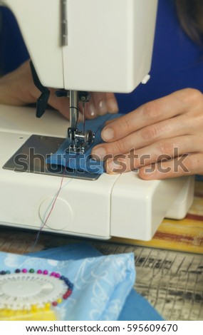 Hands on the sewing machine. Sewing. Handicraft. Sewing machine. Sewing needle. Hobby. Textile. The cloth. Felt.