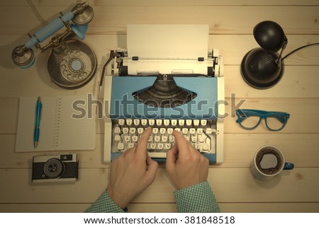 Hands on typewriter at the office desk. Flat lay.  - stock photo