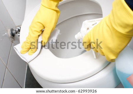 Hands on yellow gloves cleaning a WC - stock photo
