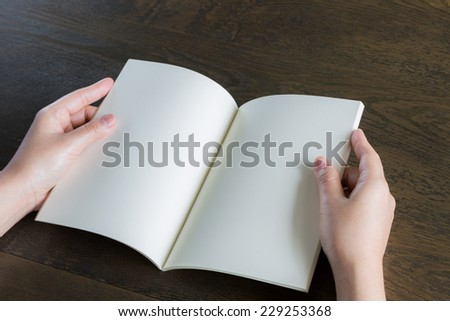 Hands open book on wood table - stock photo