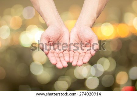 hands open palms up on blurred night city backgrounds. - stock photo