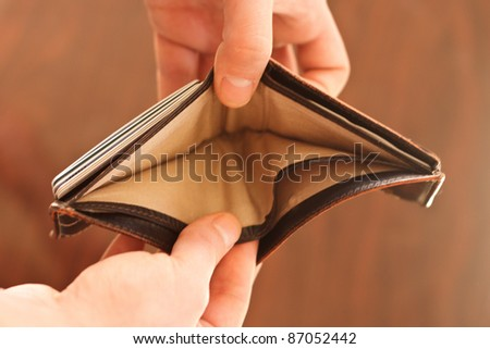 Hands opening an empty wallet against blurred background - stock photo