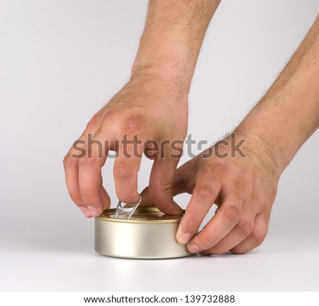 Hands opening tin can.