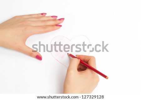 hands painting a heart with a red pencil