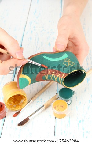Hands paints on and made ceramic saint patricks day boot and art materials  - stock photo