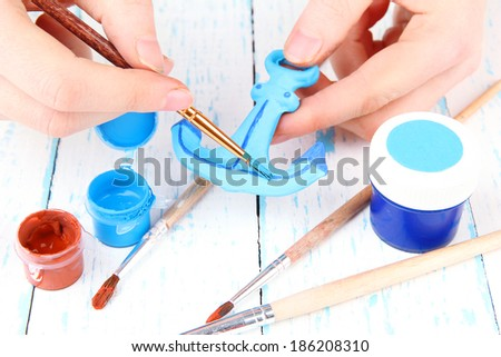 Hands paints on hand made ceramic anchor and art materials - stock photo
