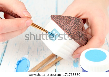 Hands paints on hand made ceramic house and  art materials - stock photo
