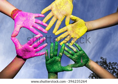 Hands / Palms of young people covered in pink, yellow, green Holi festival colors under beautiful blue sky with white clouds isolated background - stock photo